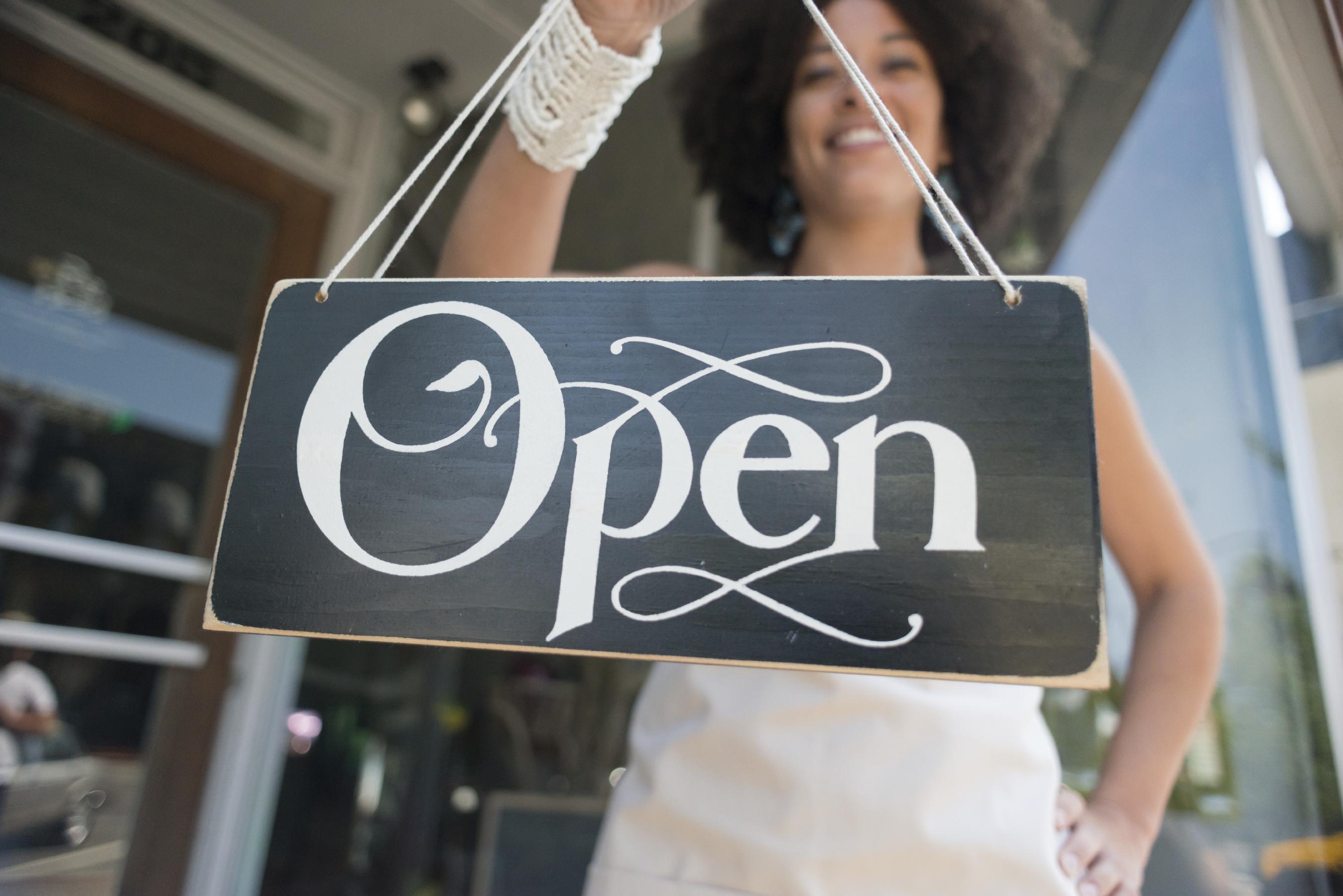 Girl Holding Business Open Sign