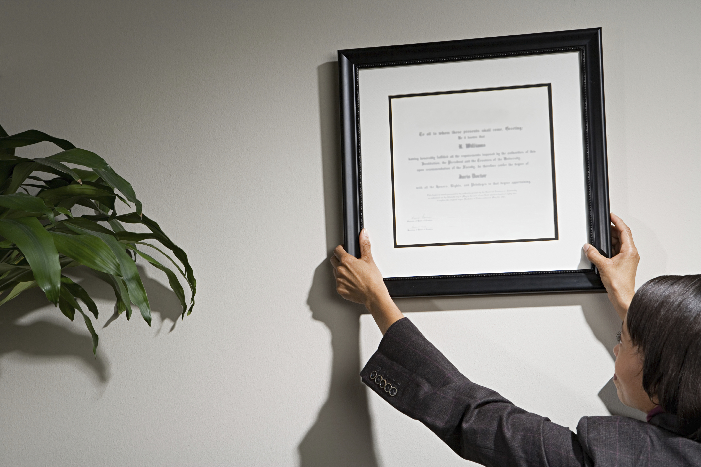 Woman Hanging Certification on the Wall